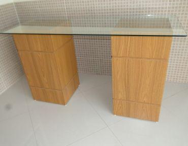 Mesa com duas bases em madeira e tampo de vidro 1,50 x 0,60 m.