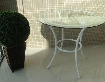 Mesa com base em ferro branco redondo com tampo de vidro de 85 cm.